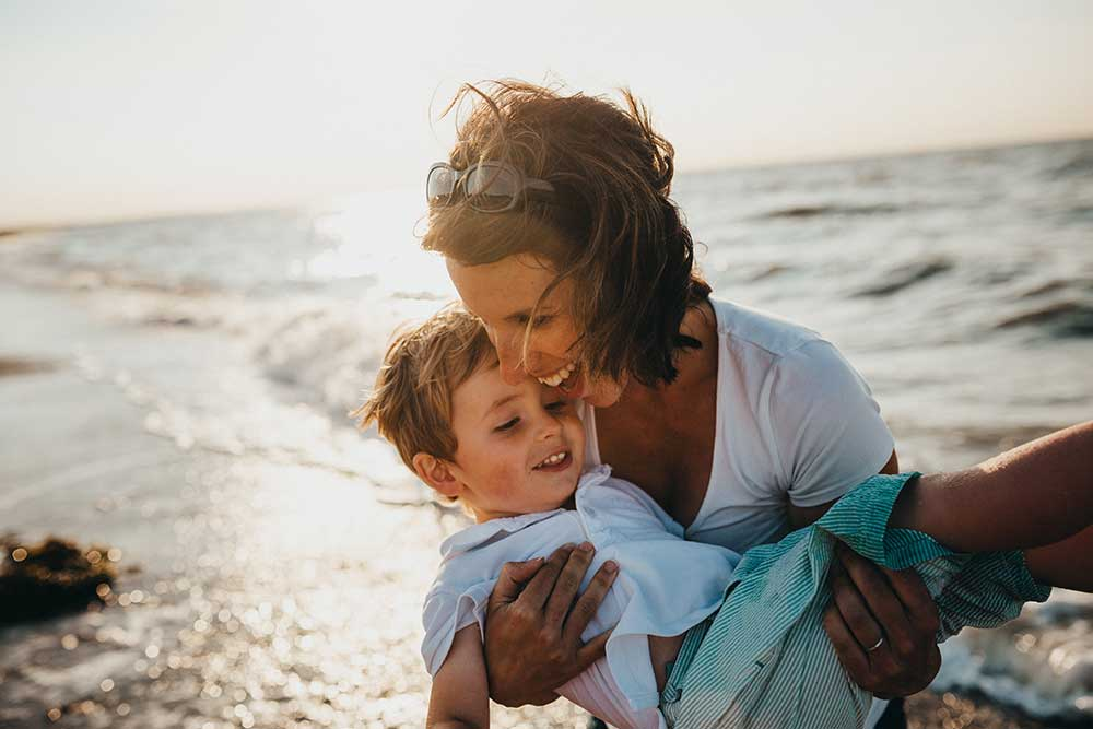Mom holding son on the beach